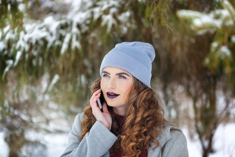Hipster Girl talking on the phone in the winter. stock photography