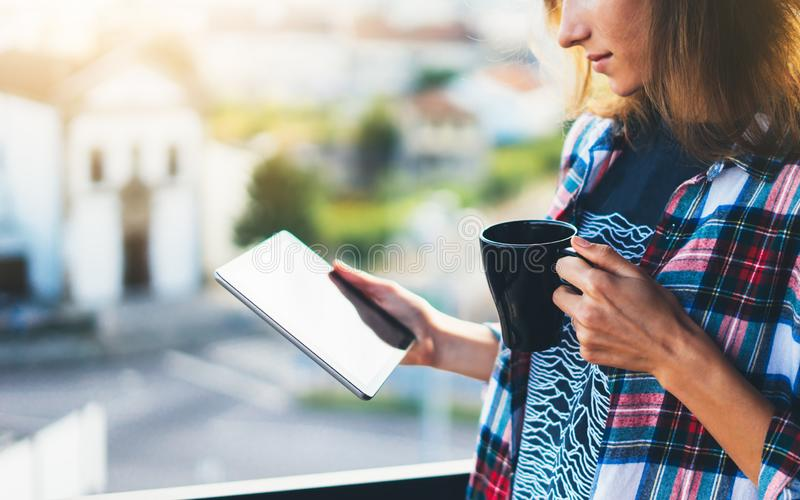 Hipster girl using tablet technology and drink coffee, girl person holding computer on background sun city, female hands texting royalty free stock photography