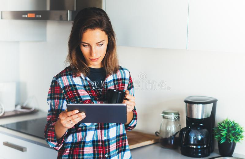 Hipster girl using tablet technology and drink coffee in kitchen, girl person holding computer on background interior cuisine, fem royalty free stock images
