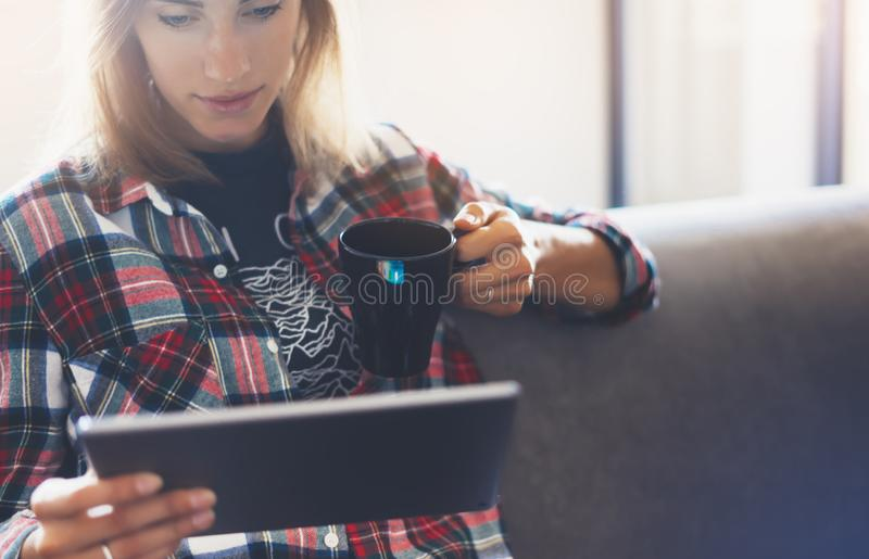 Hipster girl using tablet technology in home atmosphere, girl person holding computer with blank screen on background bokeh stock photo
