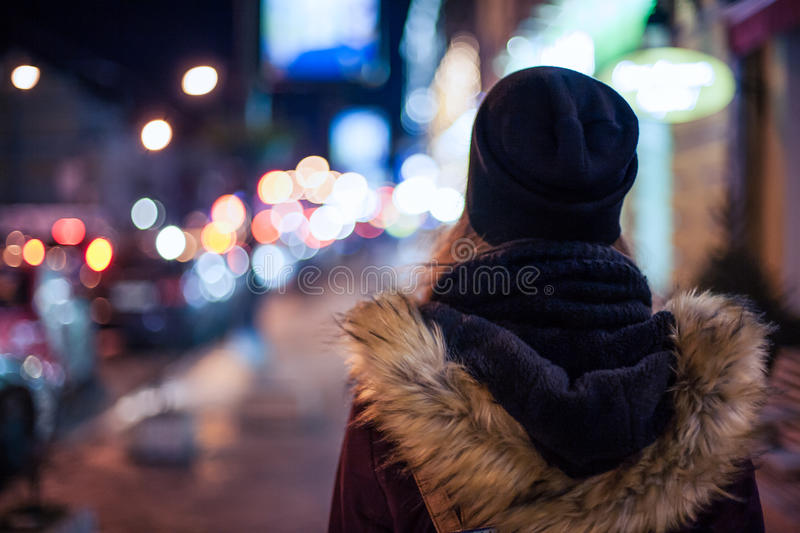 Hipster girl walking on city street at night royalty free stock photo