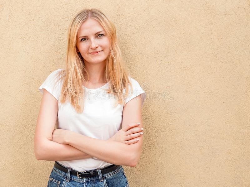 Hipster girl wearing blank white t-shirt and jeans posing against rough street wall, minimalist urban clothing style stock images