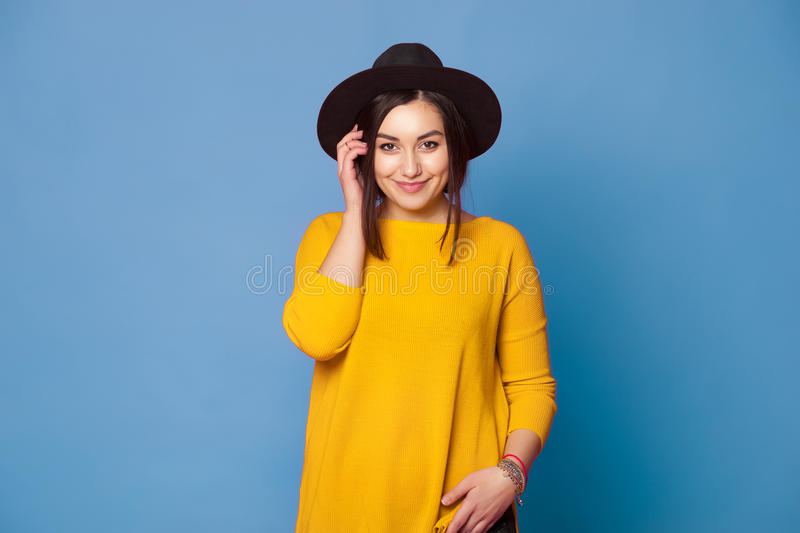 Hipster girl wearing stylish hat and yellow sweater on blue. Background royalty free stock photos