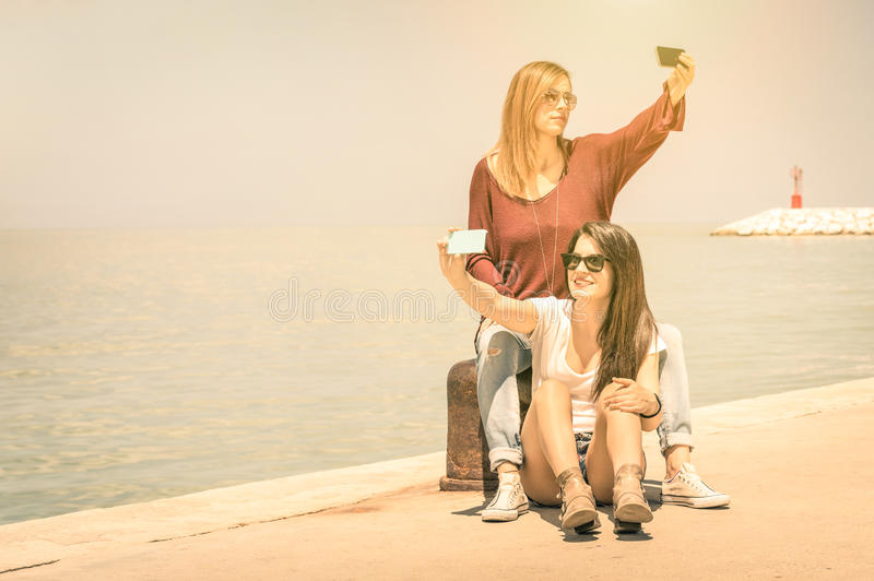 Hipster girlfriends best friends taking a double selfie. Hipster girlfriends taking a double selfie at wharf docks - Concept of friendship and fun with new stock photo