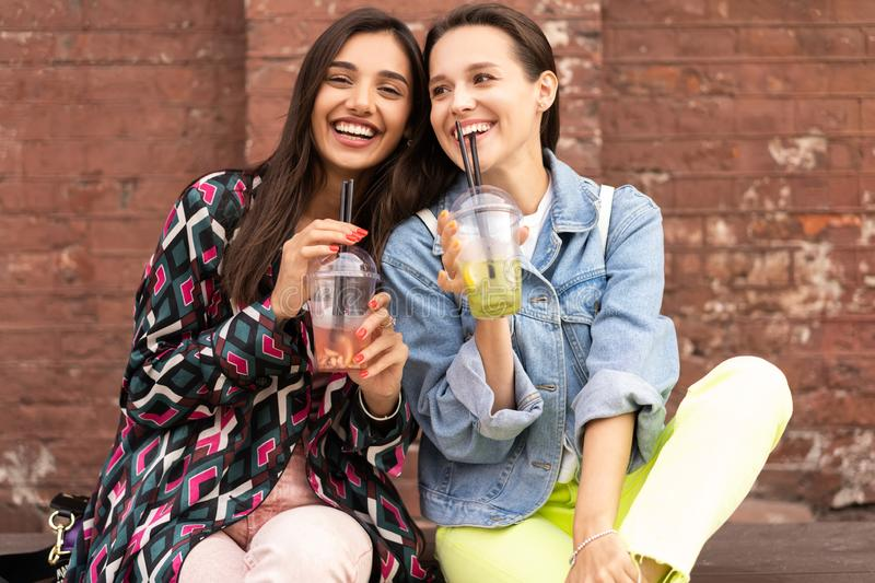 Hipster girlfriends drink cocktail in urban city background stock photos