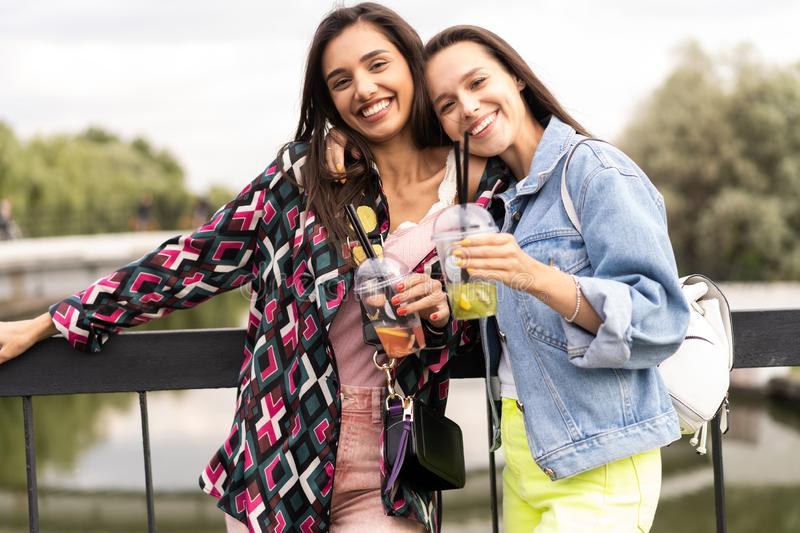 Hipster girlfriends drink cocktail in urban city background stock images