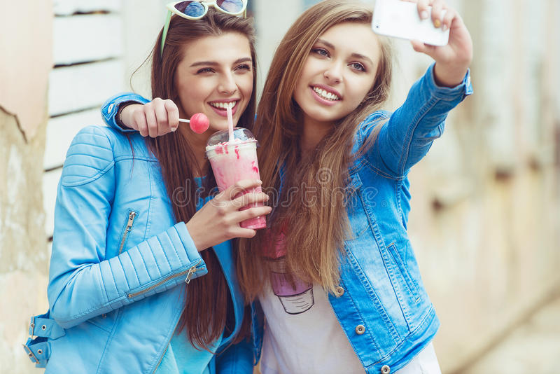 Hipster girlfriends taking a selfie in urban city stock image