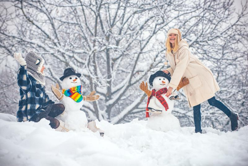 Hipster Girls friends playing with Snowman on snow Winter landscape. Christmas preparation - funny girls make snowman stock images