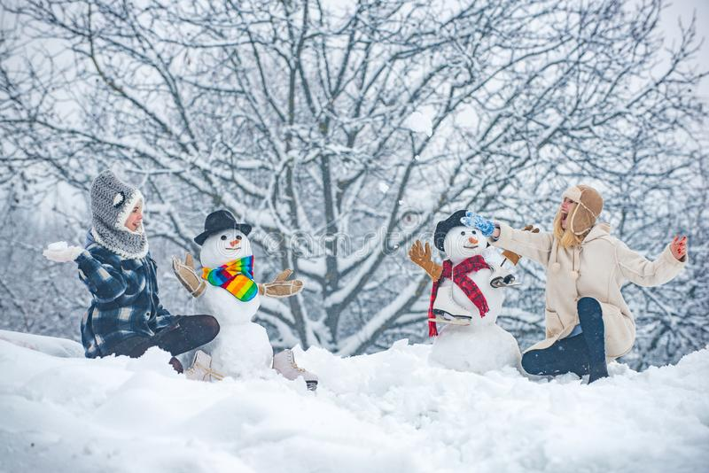 Hipster Girls friends playing with Snowman on snow Winter landscape. Winter girls. Fashion portrait of two young model royalty free stock images