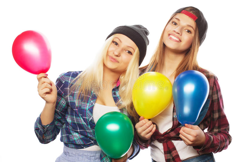 Hipster girls smiling and holding colored balloons. Two happy hipster girls smiling and holding colored balloons over white background stock photos
