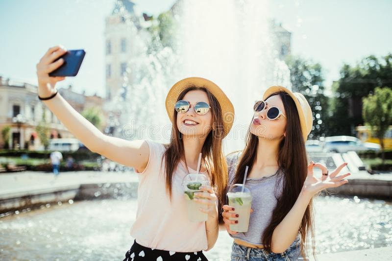 Hipster young girls in sunglasses best friends drink cocktails doing self photo and laughing in city street royalty free stock images