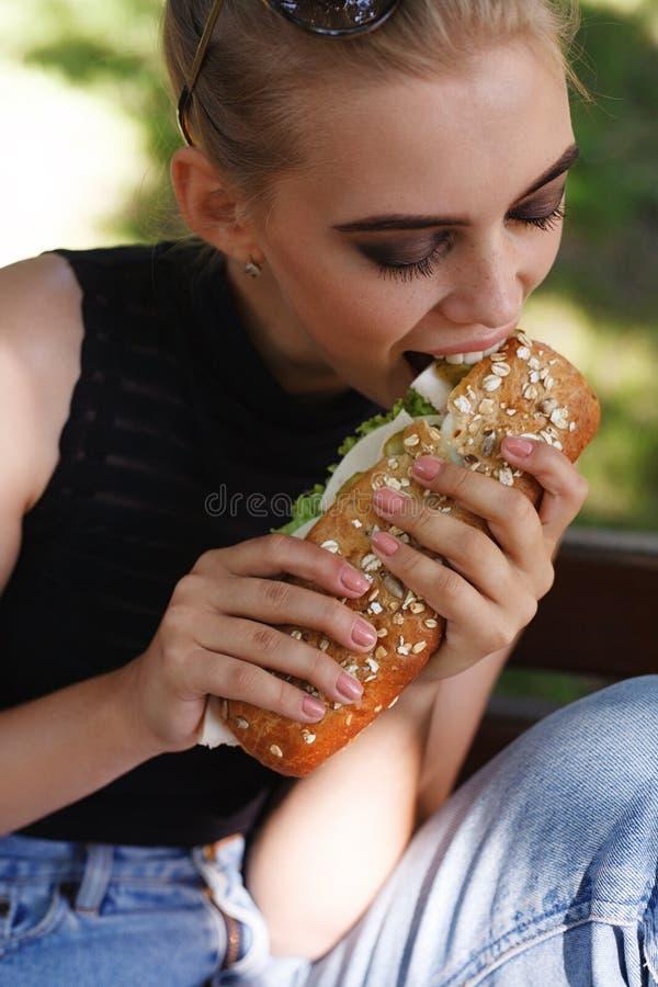 Hipster girt posing eating big sandwich stock images
