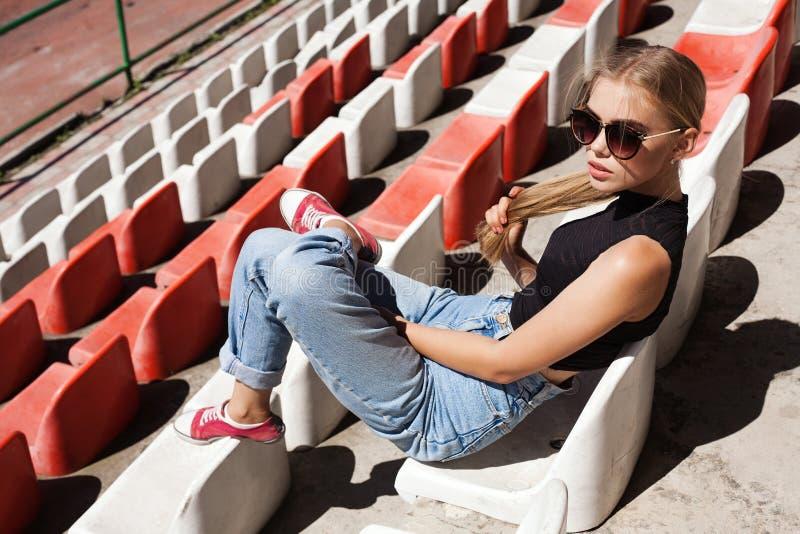 Hipster girt posing at the stadium. stock image