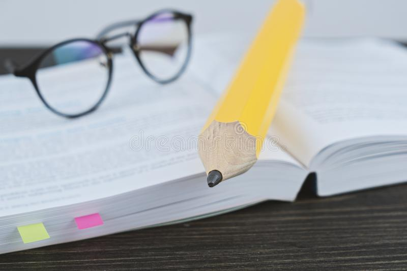 Hipster glasses for reading on an open book with big yellow pencil. Close up of hipster glasses for reading on an open book with big yellow pencil in office royalty free stock photography