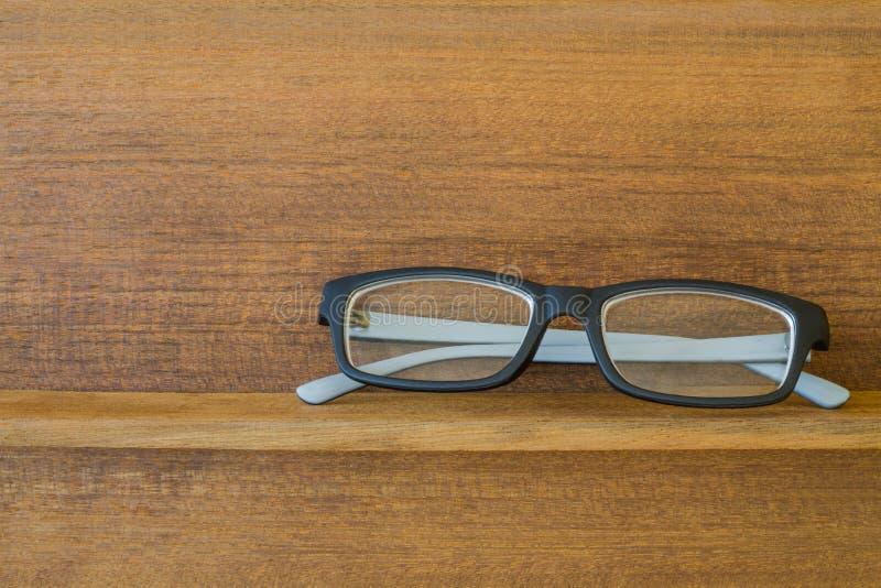 Hipster glasses on wood shelf. Black hipster glasses on old wood shelf royalty free stock photos
