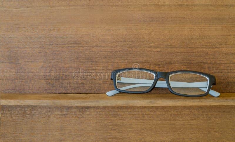 Hipster glasses on wood shelf. Black hipster glasses on old wood shelf stock photo