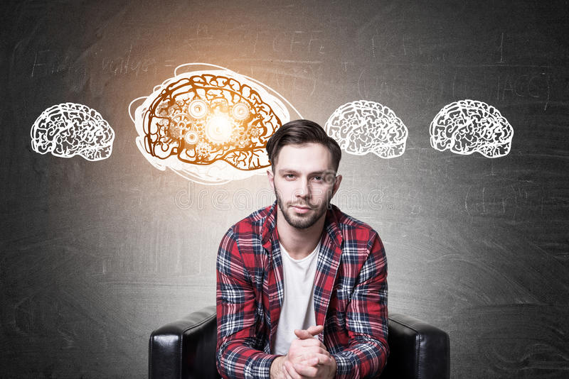 Hipster guy in an armchair and four brain cogs. Portrait of a bearded hipster guy wearing a checkered shirt and sitting in a leather armchair near a blackboard royalty free stock photos