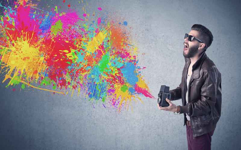 Hipster guy with camera and paint splash. A retro hipster male taking photograph with a vintage camera of an urban wall with paint splatter concept stock photos