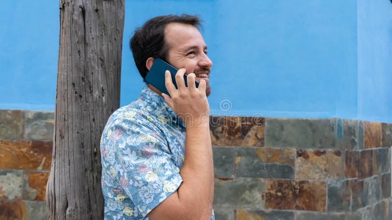 Hipster guy leaning in pole speaking by cellphone having a dialogue with his friend, consulting. Trendy person using telephone in royalty free stock images