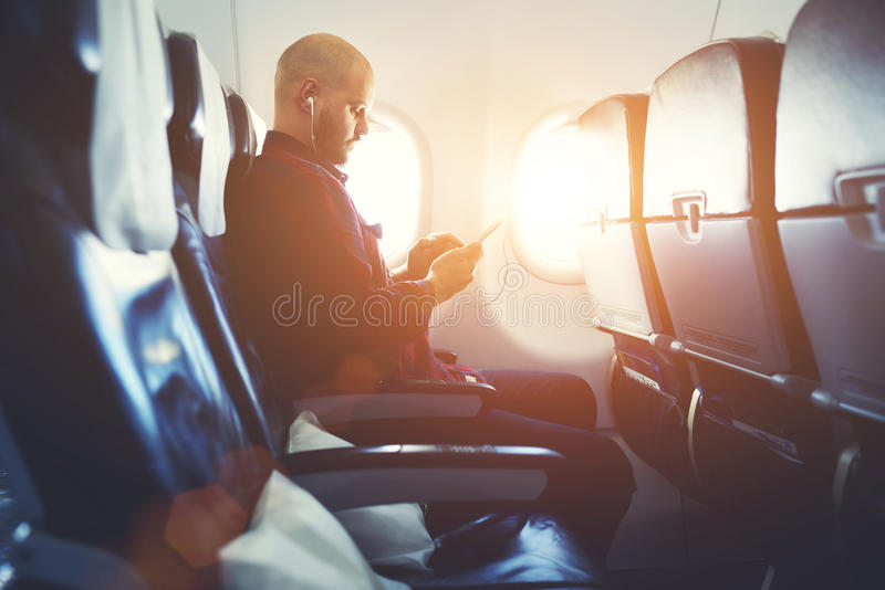 Hipster guy is listening to music in headphones via cell telephone. Man entrepreneur is watching video on mobile phone, while is sitting in plane near window