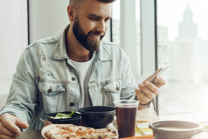 Hipster guy sits in cafe at table, has lunch, using smartphone. Man pays order in restaurant using mobile application stock image