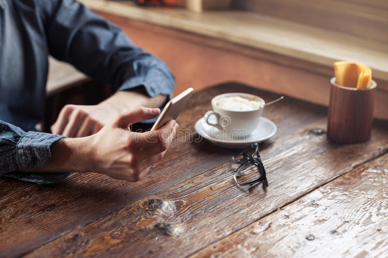 Hipster guy texting with his mobile phone stock photography