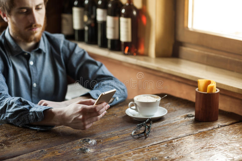 Hipster guy texting with his mobile phone stock photos