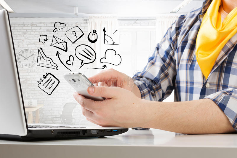 Hipster guy use laptop. Close view of guy in checked shirt using mobile phone and laptop royalty free stock image