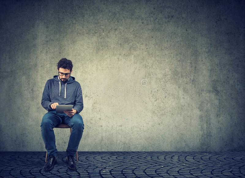 Hipster guy using tablet sitting on chair stock image