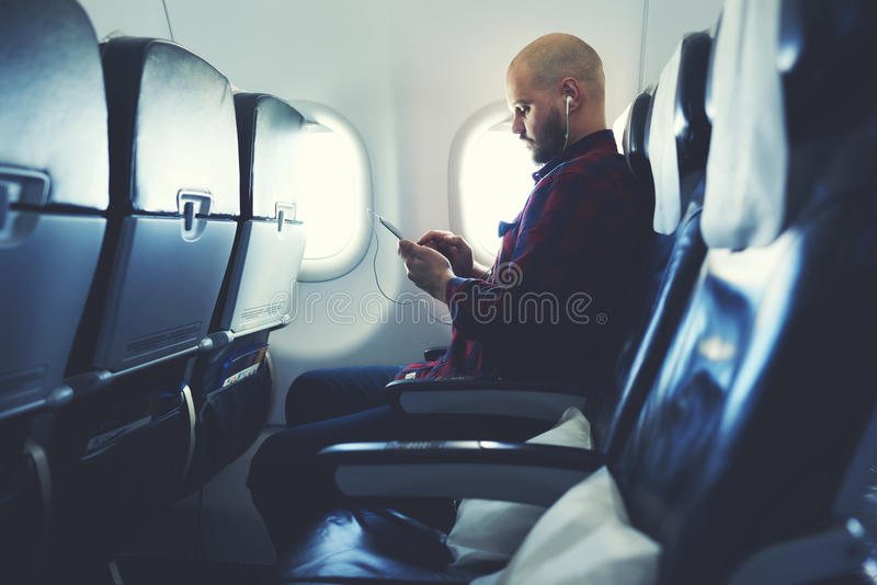 Hipster guy is watching video on cell telephone , while is sitting in plane royalty free stock photography
