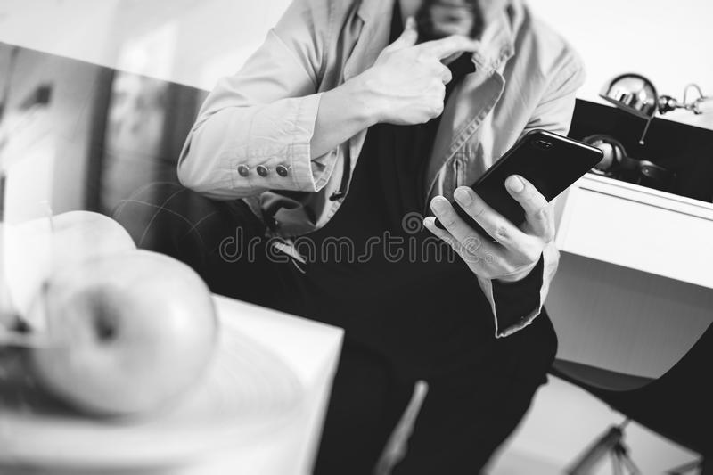hipster hand using smart phone for mobile payments online business,sitting on sofa in living room,holding green apples in wooden royalty free stock photography