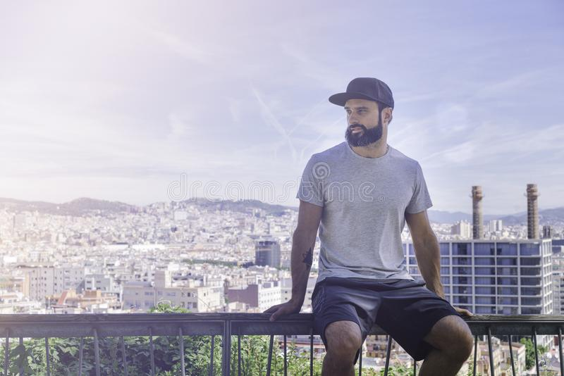 Hipster handsome male model with beard wearing gray blank t-shirt and a black snapback cap with space for your logo or. Design in casual sport urban style.View royalty free stock photo