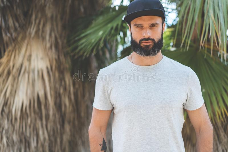 Hipster handsome male model with beard wearing gray blank t-shirt and a black snapback cap with space for your logo or royalty free stock image
