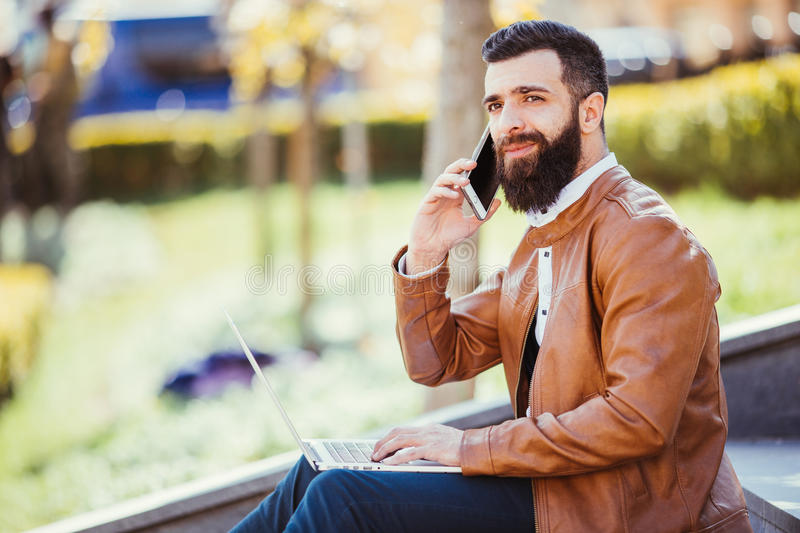 Hipster handsome young man sitting next to his laptop on the stairs while talking on his phone royalty free stock photography