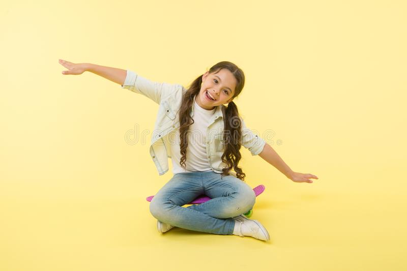 Hipster happy child pretend flying on penny board on yellow background. Little girl dream of sky with arms outstretched. Like wings. Enjoying skateboarding stock photo