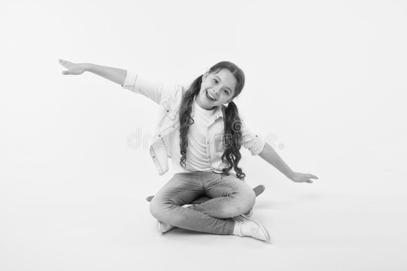 Hipster happy child pretend flying on penny board on yellow background. Little girl dream of sky with arms outstretched. Like wings. Enjoying skateboarding royalty free stock images