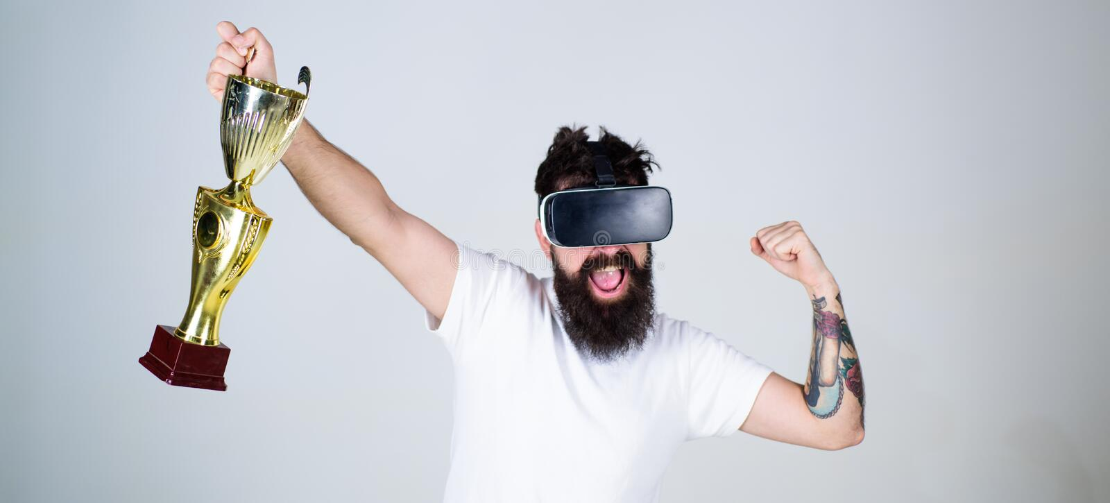 Hipster on happy face squeezing fist as successful gesture. Guy with head mounted display won in virtual game. Champion royalty free stock photography
