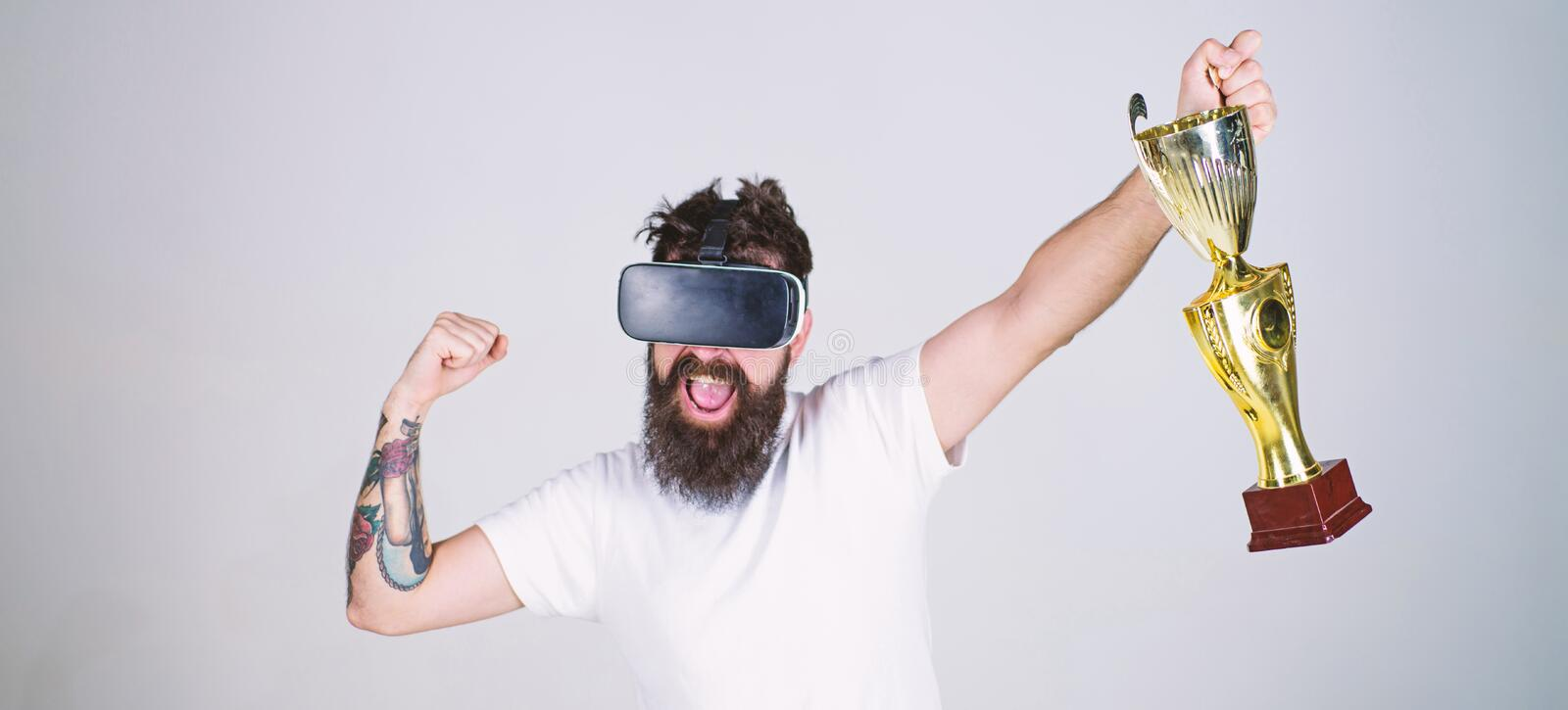 Hipster on happy face squeezing fist as successful gesture. Guy with head mounted display won in virtual game. Champion. Concept. Man with beard in virtual stock photography