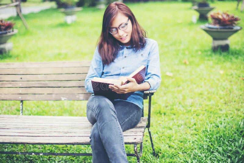 Hipster het charmante meisje ontspannen in het park terwijl het gelezen boek, van aard rond geniet stock fotografie
