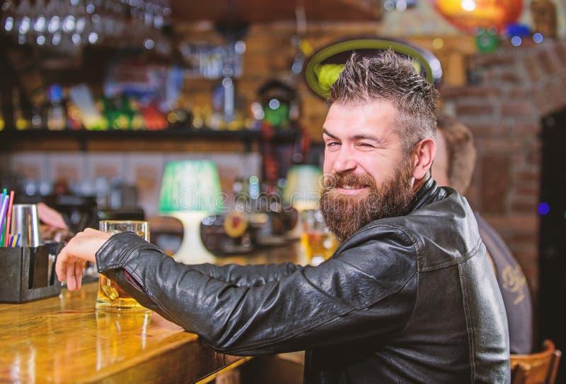 Hipster het ontspannen bij bar met bier De brutale hipster gebaarde mens zit bij barteller drinkt bier De drank van de ordealcoho royalty-vrije stock foto