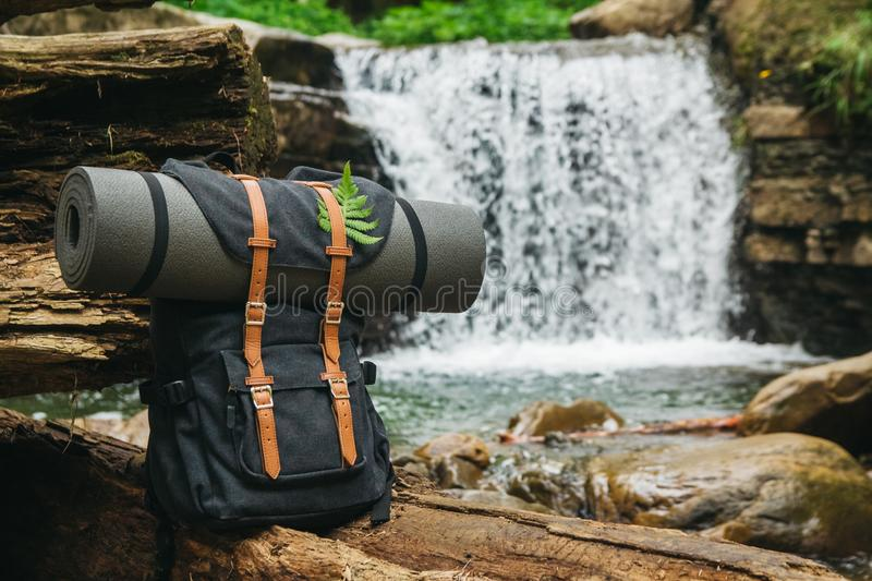 Hipster hiker tourist backpack on the background of the river and the waterfall , traveler relax holiday concept, travel. Adventure stock photos