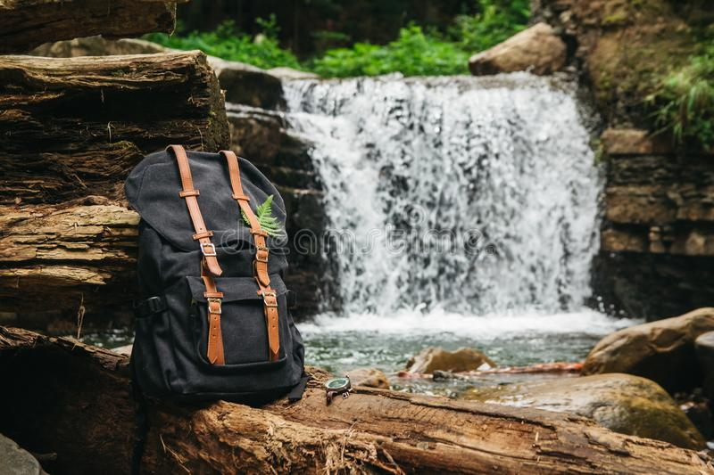 Hipster hiker tourist backpack on the background of the river and the waterfall , traveler relax holiday concept, travel. Adventure stock photo