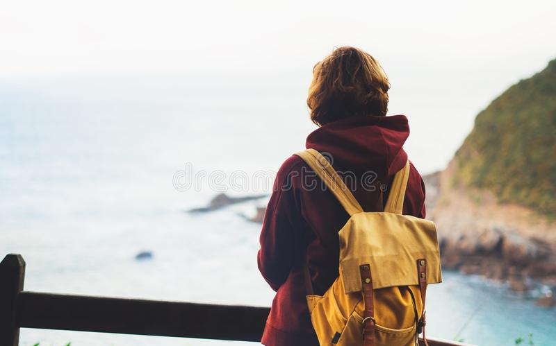Hipster hiker tourist with backpack looking on seascape sunset, background blue sea and mountain, girl enjoying ocean horizon stock image