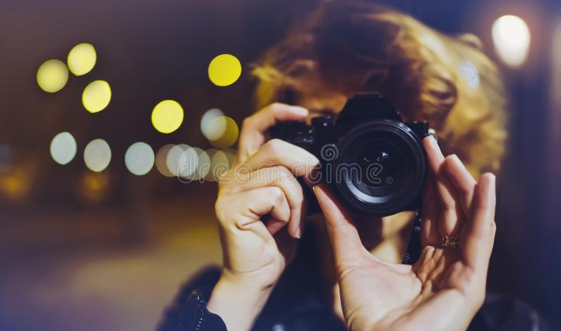 Hipster hiker tourist making photo, holding in hands camera on background of evening atmospheric city, blogger view in holiday royalty free stock photos