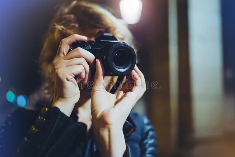 Hipster hiker tourist making photo, holding in hands camera on background of evening atmospheric city, photographer girl enjoy stock images