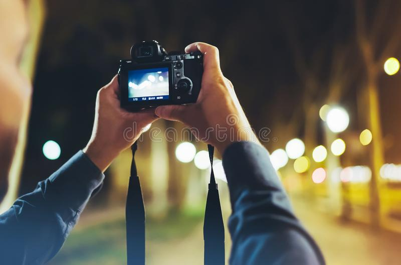 Hipster hiker tourist taking photo on camera on background of evening atmospheric city, photographer guy enjoying light of holiday. Blurred traveler relax stock photography