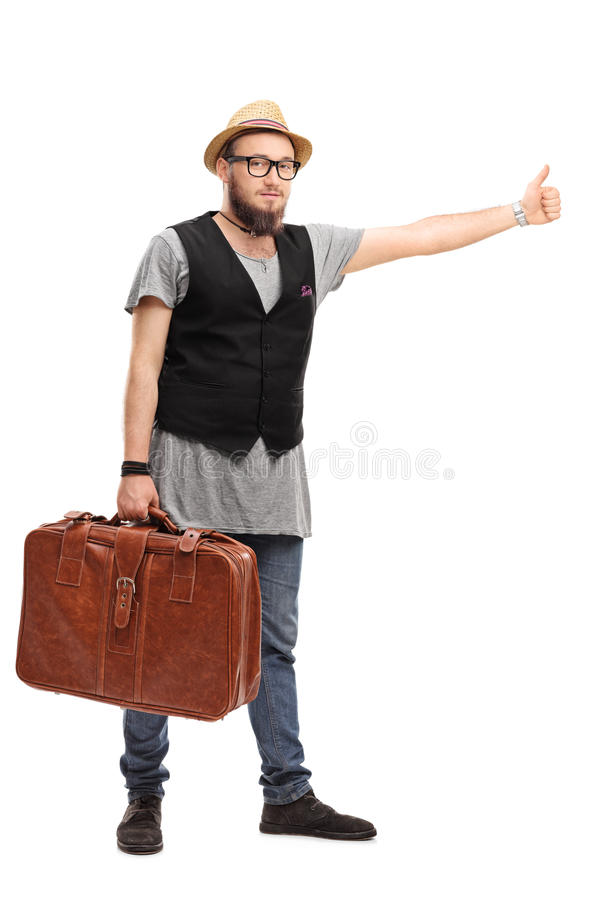 Hipster hitchhiking with his thumb. Full length portrait of a young hipster holding a brown suitcase and hitchhiking with his thumb isolated on white background stock photography