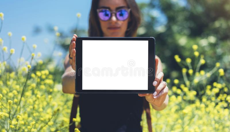 Hipster holding in hands tablet computer. Girl traveler with sunglasses using gadget on sun flare and yellow flowers background royalty free stock photos