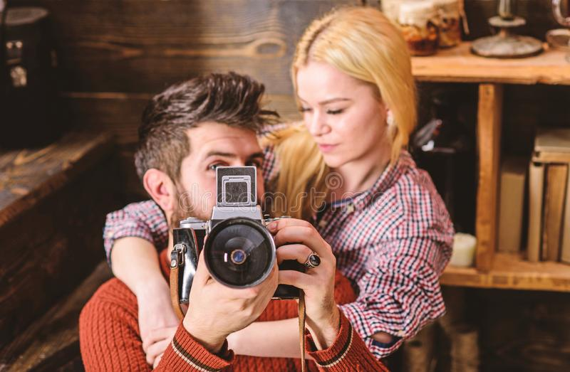 Hipster holding vintage camera while girlfriend hugs him. Vintage photographer concept. Couple in love spend romantic royalty free stock photos