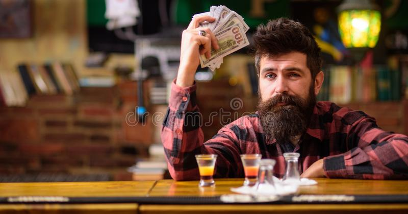 Hipster holds money, counting cash to buy more alcohol. royalty free stock photos